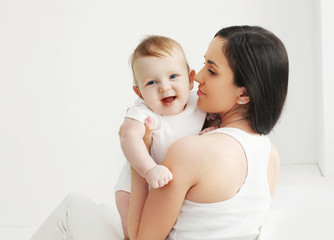 Portrait of smiling baby with mother at home in white room