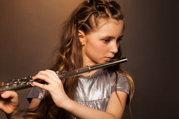 Close-up view of girl playing on silver flute