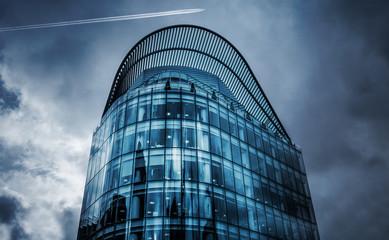 Modernes Glasgebäude mit Flugzeug am Himmel