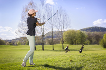 Woman golf player pitching.