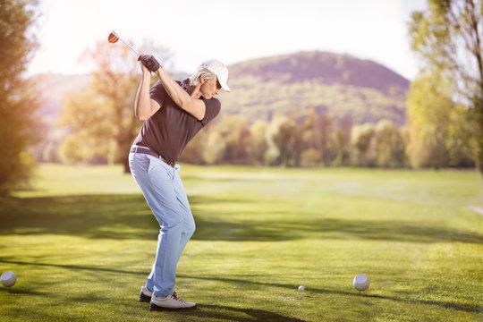 Old man swinging golf club.