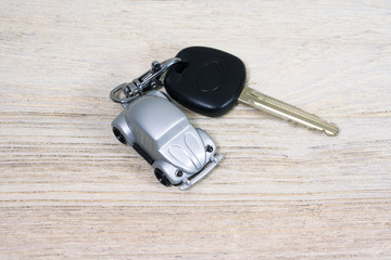Car toy with car key on white wooden table