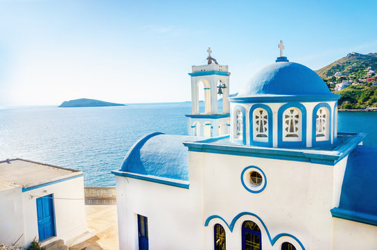 Typical Greek blue dome of white church with sea view in sunny d