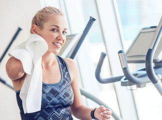 Sporty woman with towel in gym after training