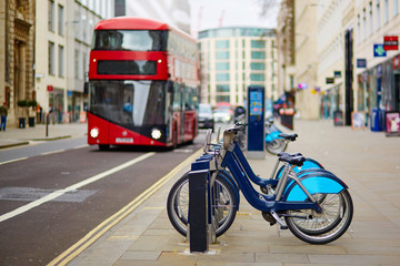 Photo on textile frame London red bus Row of bicycles for rent in London, UK