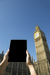 Hands Holding Tablet at Big Ben Westminster Palace London