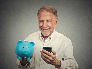 happy senior man holding piggy bank looking at smart phone