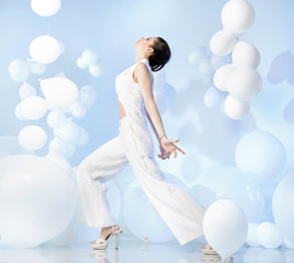 Fashion shot of adorable woman in studio full of balloons