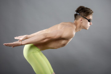 Profile of young , caucasian athlete swimmer with goggles in sta
