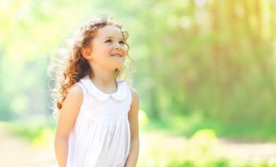 Portrait of charming curly little girl enjoying summer sunny day