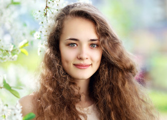 Spring portrait of a beautiful young girl with curly hair in a f