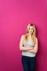 selbstbewusste junge frau lehnt an rosa wand