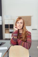 zufriedene junge mitarbeiterin sitzt im büro