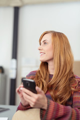 moderne junge frau mit ihrem handy im büro