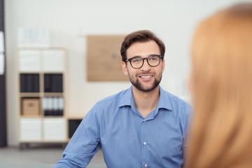 zwei leute unterhalten sich in einem büro