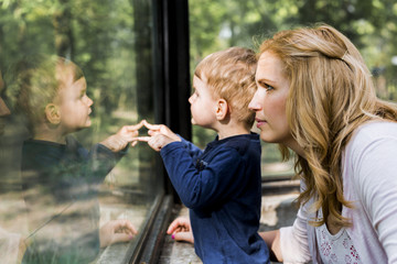 Beautiful woman holding her son with his reflection showing on t