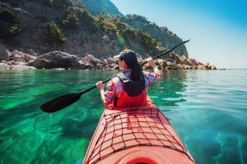 Woman kayaking at sea along rocky shore of island. Traveling