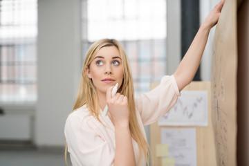kreative junge mitarbeiterin notiert ideen an einem chart