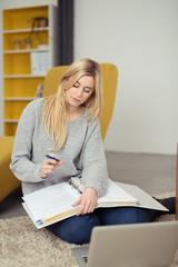 junge frau arbeitet zuhause mit unterlagen und laptop