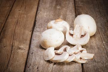 Fresh Organic mushrooms champignons on wooden background