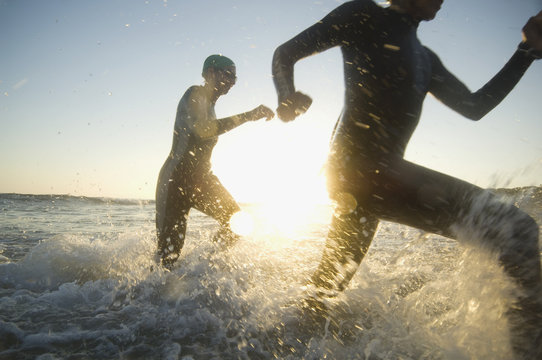 Multi-ethnic swimmers running in surf