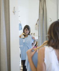 Woman holding shirt up to body in fitting room