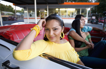 Hispanic woman with friends in convertible