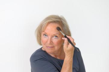 Attraktive ältere Rentnerin trägt sich Rouge auf