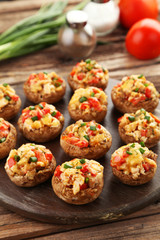 Stuffed mushrooms on cutting board on brown wooden background