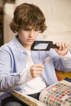 Hispanic boy examining stamp through magnifying glass