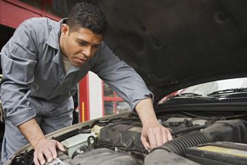 Hispanic male auto mechanic under hood of car