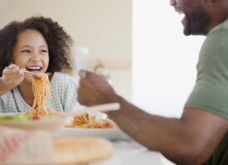 African father and daughter eating pasta