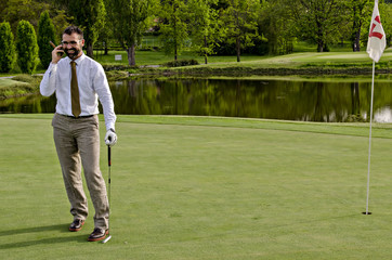 Businessman on phone while playing golf