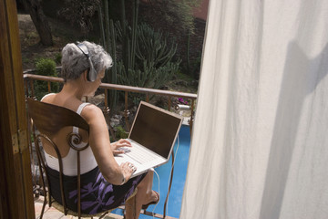 Senior Hispanic woman typing on laptop