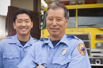 Asian male paramedics in front of ambulance