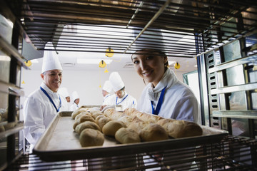 Asian female baker taking tray of bread off rack