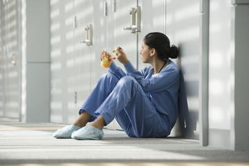 Hispanic nurse eating fruit on floor