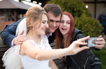 happy bride and groom making selfie with guest on wedding day