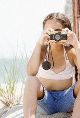 Hispanic girl taking photograph on beach