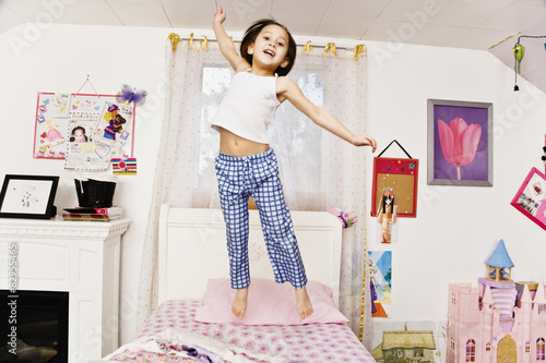 Asian girls jumping on bed