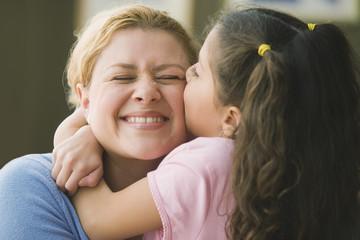 Hispanic girl kissing mother's cheek