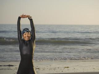 Asian woman stretching in wetsuit and goggles
