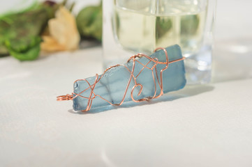 Handmade pendent from glass and a copper wire close up