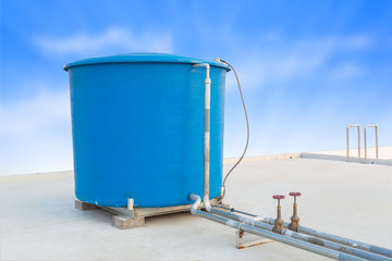 Blue water tank of industrial building on roof top and blue clou