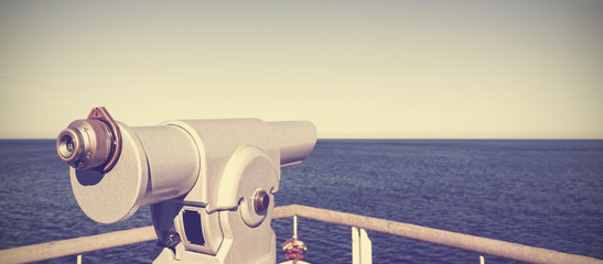 Vintage toned photo of a telescope pointed at the horizon.