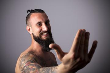 Joven hipster tatuado con mano alzada