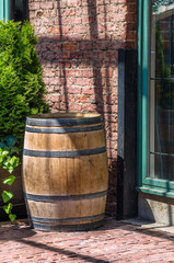 Traditional Wooden Barrel Standing in front of a Brick Wall