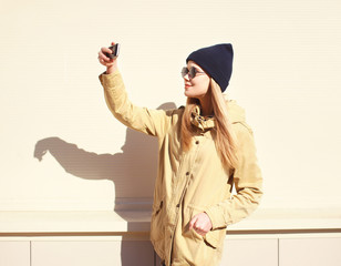 Fashion pretty blonde makes selfie-portrait on the smartphone, c
