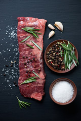 Raw machete steak with sea salt, pepper, garlic and rosemary