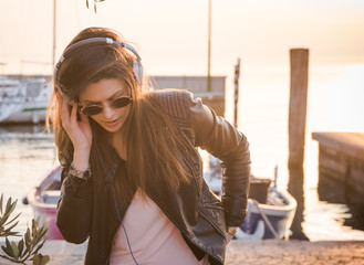 Young woman in headphones listening music and enjoying beautiful sunset over the sea.